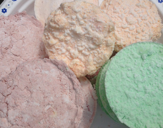 Floral scented, orange scented, and mint scented bath bombs created in a muffin pan without a lid.
