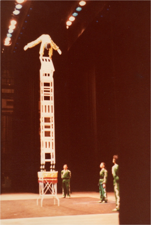 I took this photo from the side of the stage.  Chang Yu Ching is balancing on a tilted chair while at the top of a pagoda of chairs supported at the base by nothing more than the tops of four bottles.  He could go higher, but for the lights.