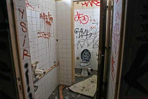 A restroom with its own gang graffiti.