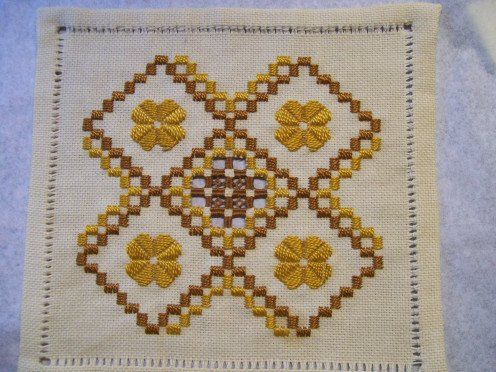 Hardanger done with gold and medium brown pearl cotton threads. With Hem stitching border.