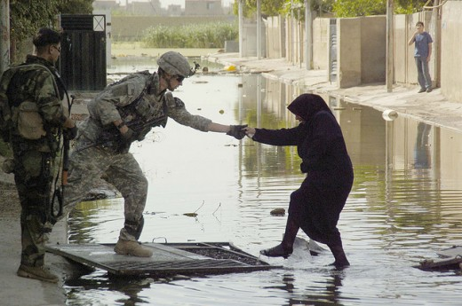 A soldier helping an Iraqi woman cross a water-filled street.