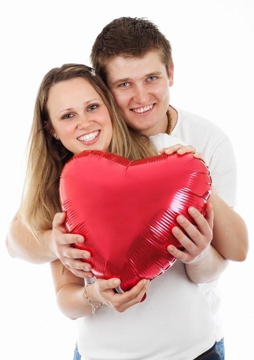 A couple holding a heart-shaped balloon.