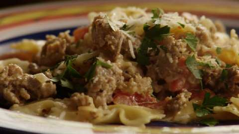 Italian Sausage Primavera, served over bowtie pasta, garnished with parsley and fresh grated romano cheese.