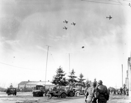 """""""Watching C-47's drop supplies"""". Licensed under Public Domain via Wikimedia Commons"""