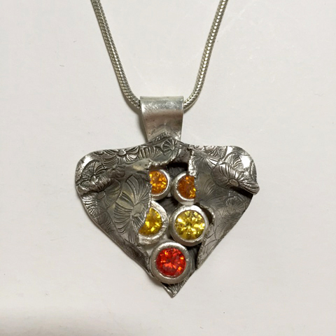 "The finished class project for Patrik Kusek's online class, ""Silver Metal Clay: Adding Stones & Dimension"" is this dimensional, multi-layered, fine silver pendant with a cluster of bezel set gemstones."