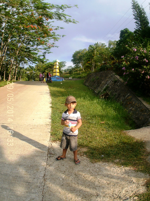 A toddler standing at the road side fronting Sagbayan Peak.