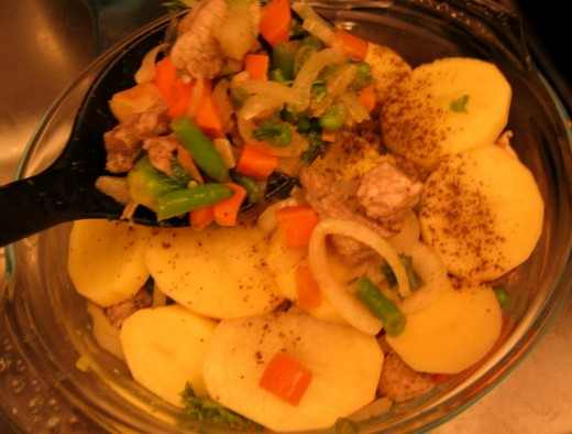 Adding a layer of the meat and vegetable mixture.
