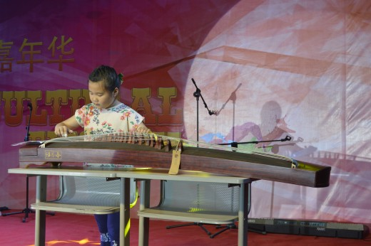A child playing a traditional Chinese insrument