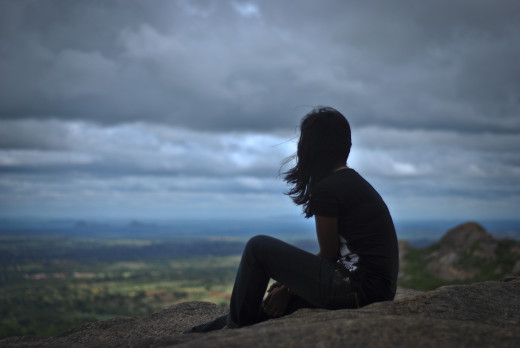 A pondering girl on top of a mountain.