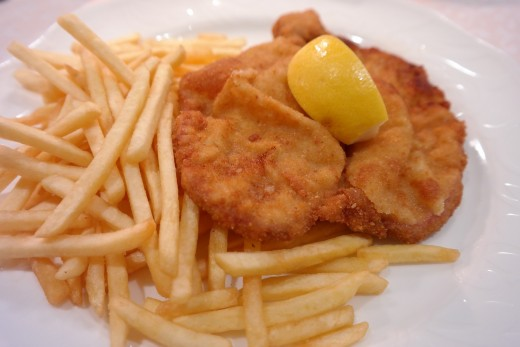 French fries served with Wiener Schnitzel, which is a flat breaded veal.
