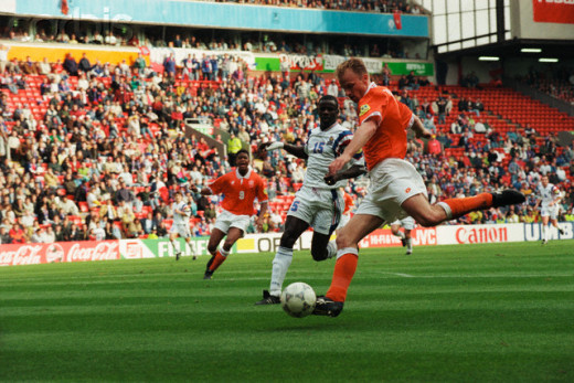 Dennis Bergkamp of the Netherlands takes a shot as France's Lillian Thuram (15) watches during a match in Liverpool, England. France defeated the Netherlands to advance to the semifinals of Euro 1996.