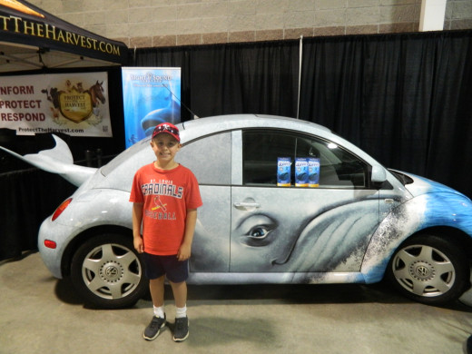 Caleb in front of a Beetle Bug dressed up to advertise Jonah and the Whale, a local show currently going on in Branson.