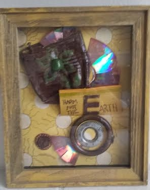 """""""Harm Not, The Earth"""": Old tin can, glossed; a screw; a cd disk, cut around the edges; a piece of reflected rubber; a combination lock facing; a painted pebble, and other miscellaneous."""