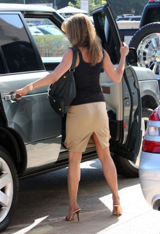 Jennifer Aniston out and about in a skirt and mule high heels.