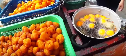 A screenshot of a street vendor deep-frying battered quail eggs for one customer. It's so delicious when served while hot. You then dipped them to a container of sweet and spicy sauce for flavor and eat. So yummy that you'll be asking for more.