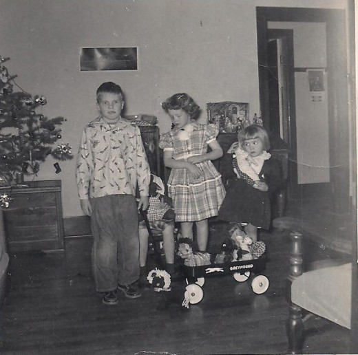 This photo brings back memories of the 1950s. We are showing off our new Christmas outfits and toys for the camera.