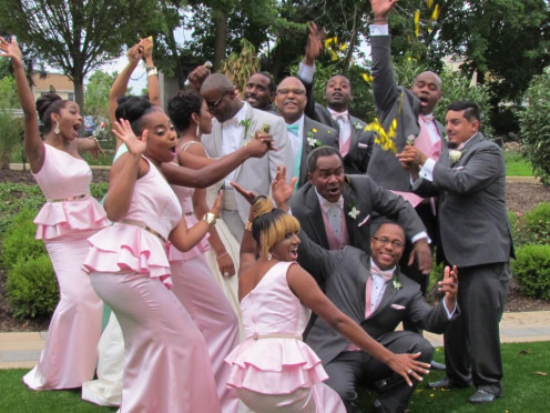 Bridal party clowns around as bride and groom are focused on a special moment.