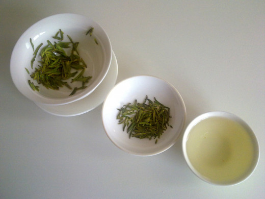 The appearance of green tea at three different stages  the infused leaves, the dry leaves, and the tea.  This particular green tea is Xu Fu Long Ya, a fine Chinese green tea from Sichuan.