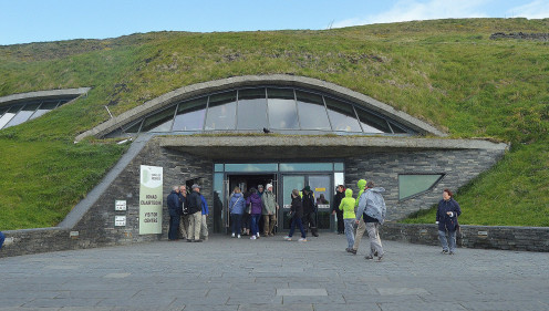 The visitors center and nearby shops blend into a hillside by the cliffs.