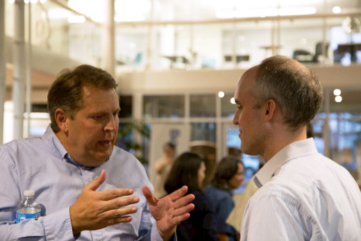 A launch party attendee (left) engages in discussion with CrowdSchool co-founder and CEO Peter Glenn (right)