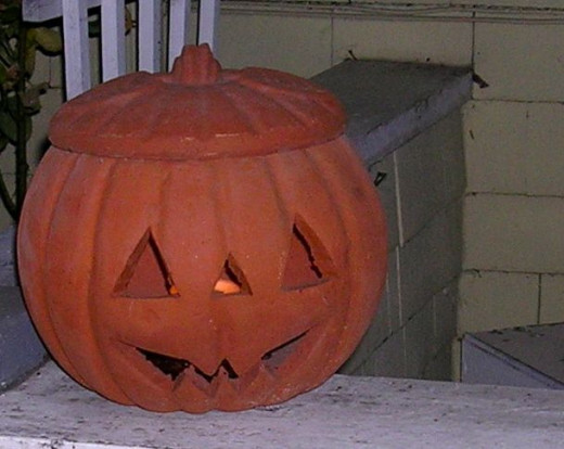 A terracotta pumpkin lights the porch for trick-or-treaters!