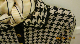 Hounds tooth cardigan sweater accessorized with a beige, black and white striped scarf