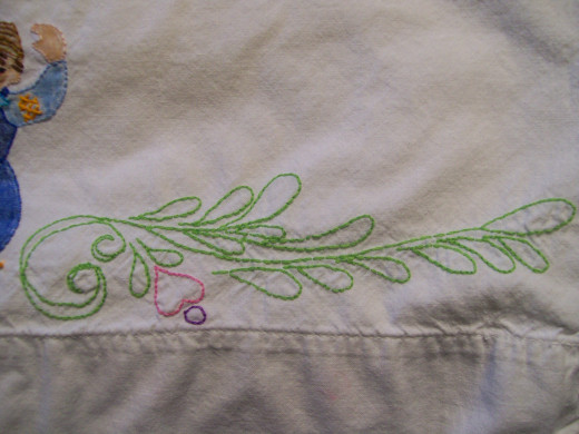 Close up of embroidered greenery on embroidery over painted parts pillow case.
