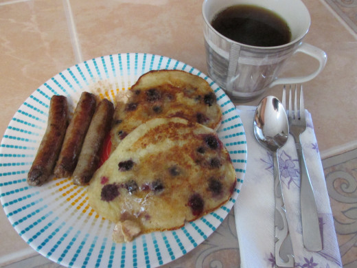 Banana, Blueberry Pancakes with the special butter melting on them, Sausage and Coffee for Breakfast.