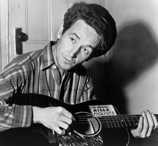 "Woody Guthrie with guitar labeled ""This machine kills fascists"" (1943)"