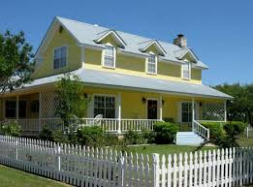 A yellow house with a picket fence