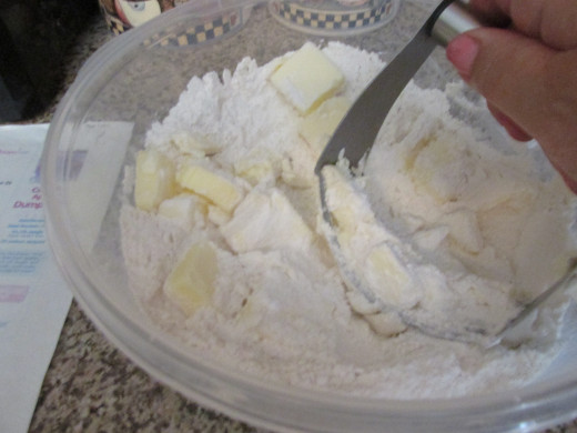 Incorporating the butter in the flour and sugar with a pastry blender.