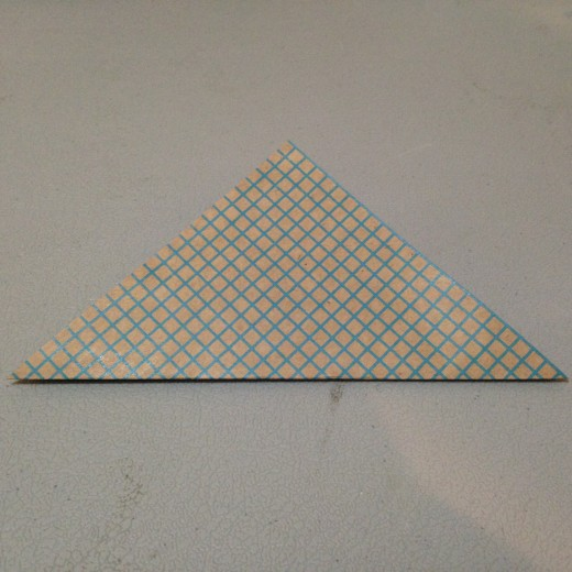 "Fold your square into a triangle. The pattern on your paper should be facing outward. If one side is ""prettier"" than the other it should face down because that will be the outside of your petal."