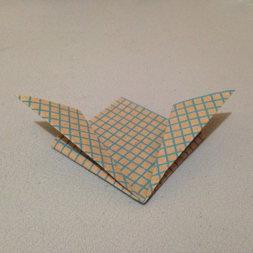 Fold these edges back out but only halfway. The two folded parts should line up on the outside. It should still be diamond shaped but with wings on top.