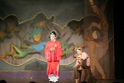 A play with the Kitchen God of Chinese Culture at the center in red.