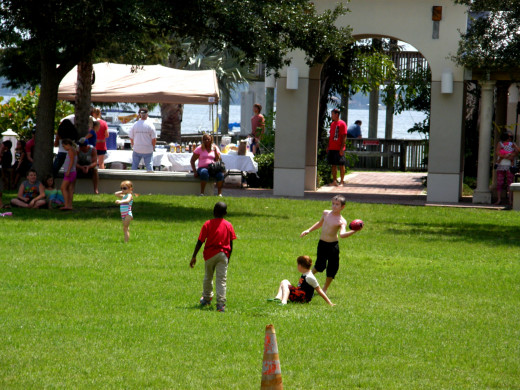 Kids enjoy a game of football on the open lawn of the Riverfront Park.