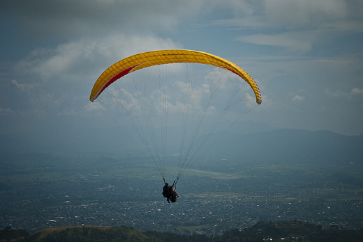 A paraglider with Pokhara airport on the background
