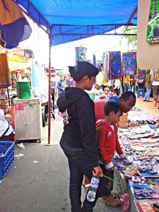 Dress down when shopping at street markets just like the family above who were looking for toys for the child at the Jalan Surabaya Flea market in Indonesia.