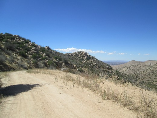 Walking down a dirt road with the view of Hesperia in the distance.