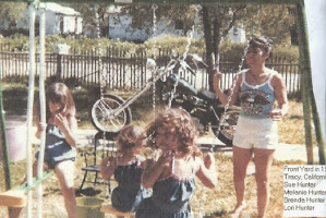 This is my dad's harley in the background. My mom is in white shorts. My two sisters and I are on the swing set.