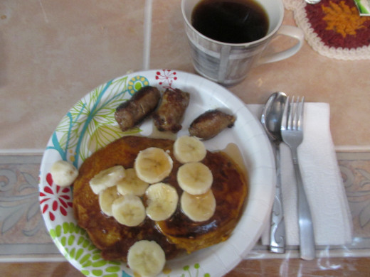 Pumpkin pancakes with fresh sliced bananas and sausage on the side and a hot cup of coffee with lots of syrup.