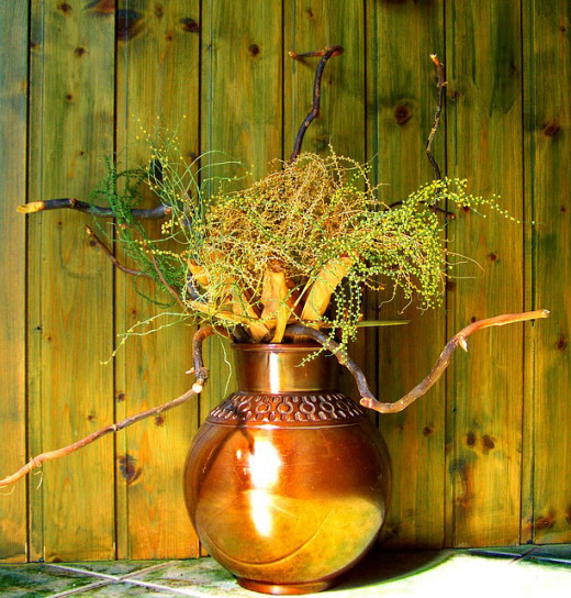 Dry flower bouquet in a gold vase.