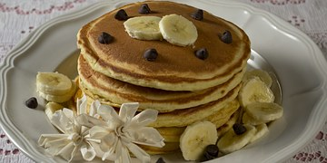 Pancakes topped with banana and chocolate chips.