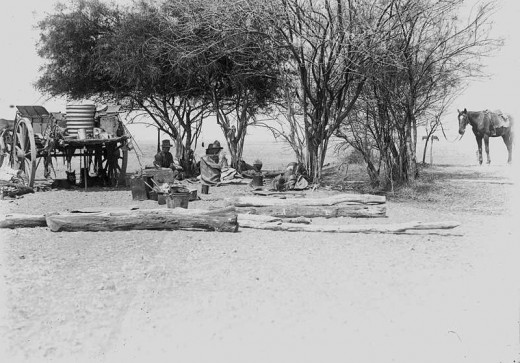 Drovers (overlanders) camping under some trees at Hughenden, Queensland. Boxes, buckets and other gear are spread out upon the ground. Dogs shelter under the loaded dray.