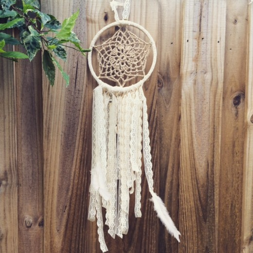 There are feathers, shells and charms at the bottom of this dreamcatcher!