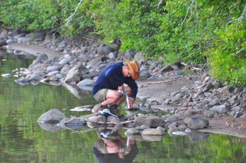 Water engineer collecting a sample to measure quality. In order to make an accurate assessment, he will take many samples from different locations and depths, carefully labeling them all before testing.