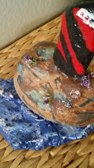 After making lighthouse, I adhered it to another rock and painted to appear like a cliff. High heat glue gun worked fine. Use heavy glue. Adhered sprigs of silk flowers. Took another rock and adhered it to bottom and painted it to look like water.