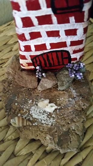 I adhered pebbles to bottom of lighthouse and sprigs of silk flowers. Adhered another rock on bottom and painted to look like dirt. After light coating of glue, added sand and sea shells.