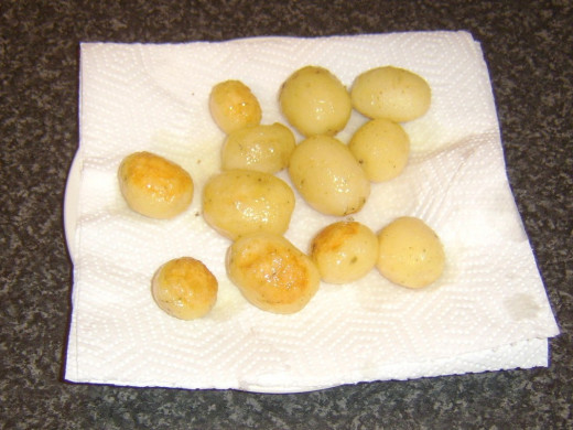 Roasted potatoes are drained on kitchen paper