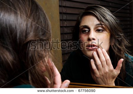 woman checks extent of her domestic violence injuries in the bathroom mirror