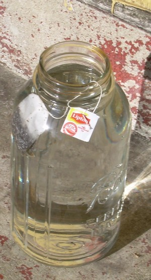 Place clear glass container with tea bags in safe location where sunlight hits all day.
